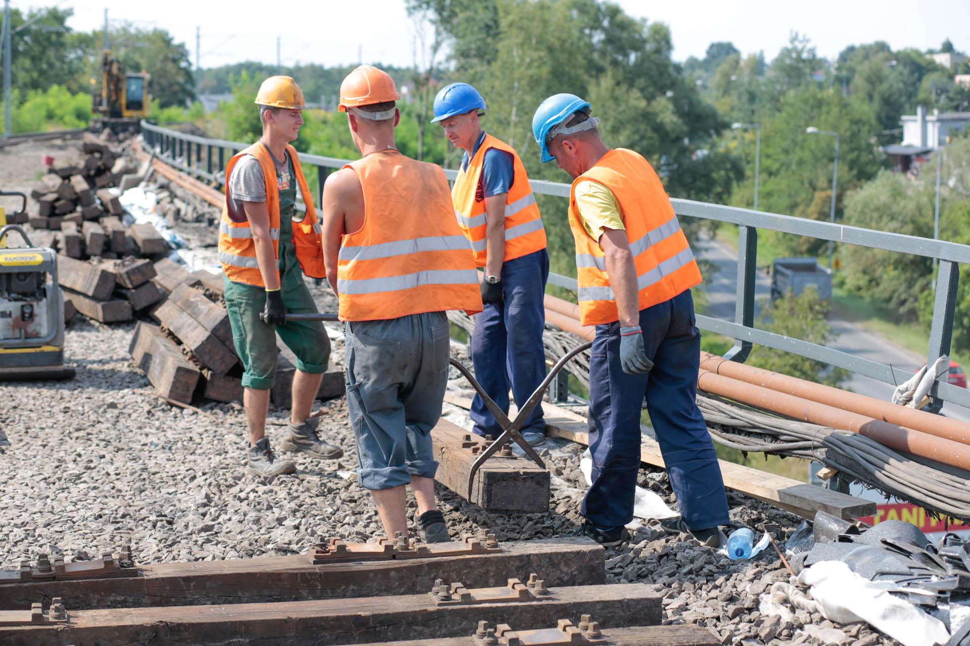 Obrazek: robotnicy przenoszą stare podkłady
