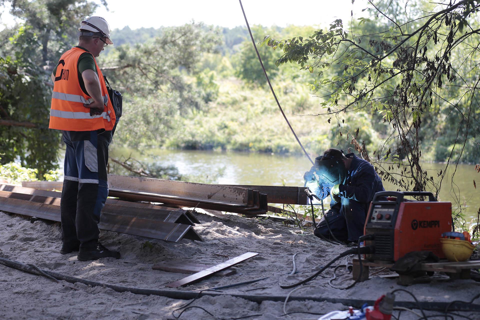 Obrazek: pracownik spawa metalową konstrukcje, drugi robotnik przygląda się temu