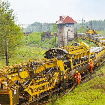 Zdjęcie: pochmurna pogoda, żółta maszyna do potokowej wymiany torowiska porusza się po torach.