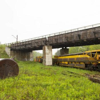 Zdjęcie: pochmurna pogoda, żółta maszyna do potokowej wymiany torowiska porusza się po torach. W tle widać wiadukt.