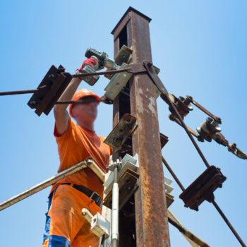 Zdjęcie: robotnik wiesza nową sieć trakcyjną.