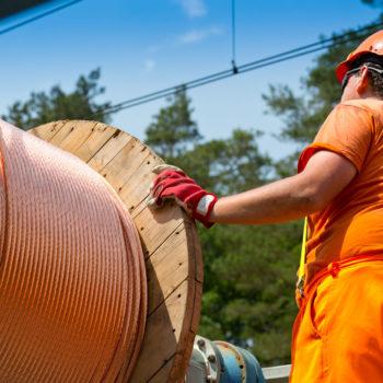 Zdjęcie: robotnik przy bębnie z siecią trakcyjną