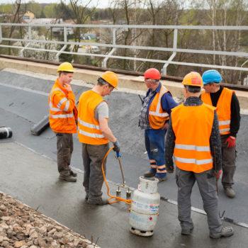 Zdjęcie: robotnicy na Moście Zamysłowki kładą uszczelnienie.