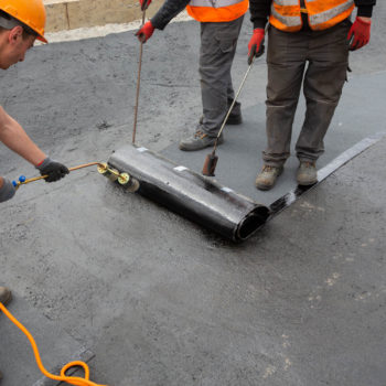 Zdjęcie: robotnicy kładą pape.