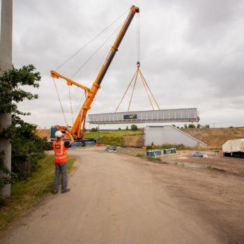 Zdjęcie: na pierwszym planie robotnik, dalej pomarańczowy dźwig podnosi przęsło wiaduktu w Toszku.