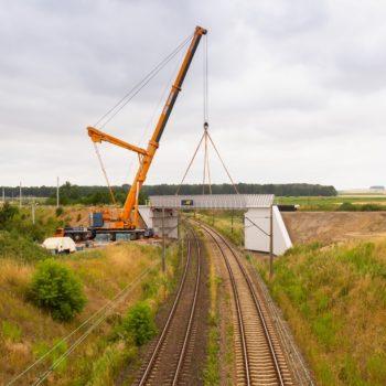 Zdjęcie: widok z daleka pomarańczowy dźwig podnosi przęsło wiaduktu w Toszku.