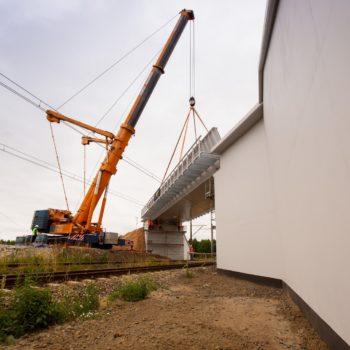 Zdjęcie: pomarańczowy dźwig podnosi przęsło wiaduktu w Toszku.