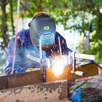 Zdjęcie: spawacz spawa metalowe elementy konstrukcji.