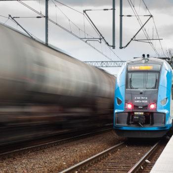 Zdjęcie: pociąg, na drugim planie rozmyty pociąg na torach.