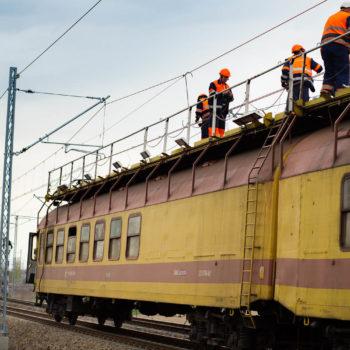 Zdjęcie: pociąg do podwieszania trakcji z robotnikami pracującymi na górze.