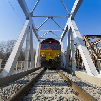 Zdjęcie: żółto czerwony pociąg stoi na wyremontowanym moście na Kanale Gliwickim.