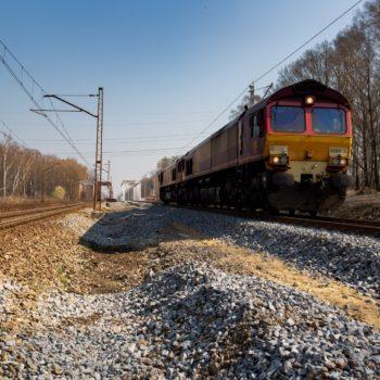 Zdjęcie: żółto czerwony pociąg porusza się po torach.