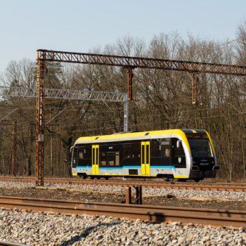 Zdjęcie: pasażerski pociąg porusza się po torach.