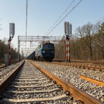 Zdjęcie: niebieski pociąg porusza się po torach.