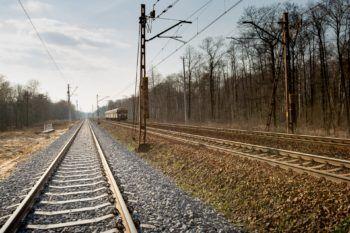 Obrazek przedstawia nowe tory z nową szarą podsypką. W tle widać stare tory a jeszcze dalej pociąg.