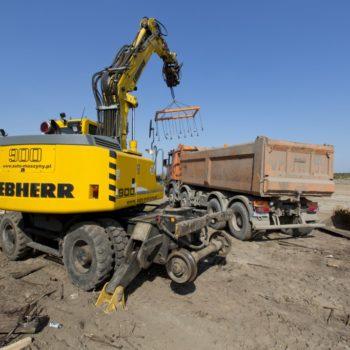 Zdjęcie: dźwig wkłada nowe podkłady kolejowe do ciężarówki.