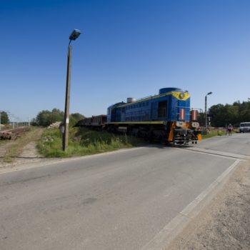 Zdjęcie: niebieski pociąg towarowy wjeżdża na przejazd kolejowo-drogowy.