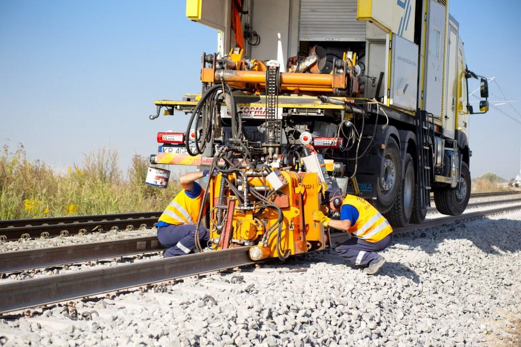 Obrazek: dwóch prasowników pochyla się nad skomplikowaną maszyną ustawioną na torach.