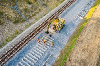 Zdjęcie: widok z lotu ptaka, koparka układa nowe podkłady kolejowe.