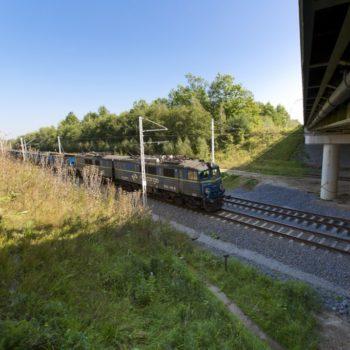 Zdjęcie: niebieski pociąg porusza się po torowisku.