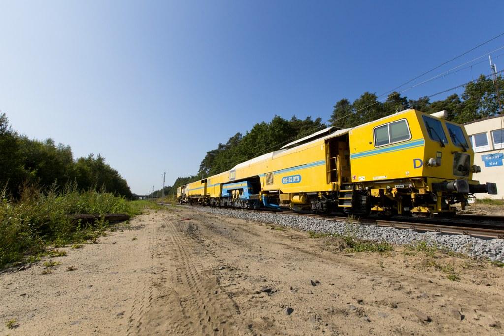Obrazek: żółty pociąg który jest zgrzewarką torową, w tle las.