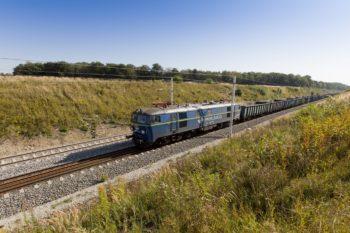 Obrazek: malowniczy krajobraz z pociągiem jadącym po torach.