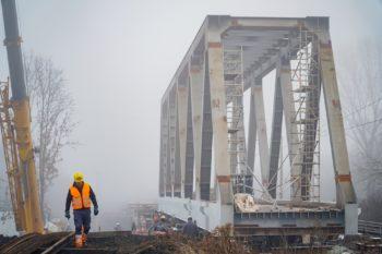 Zdjęcie: widok z ziemi na przęsło mostu na rzece Białej. Z boku idzie robotnik w pomarańczowej kamizelce.