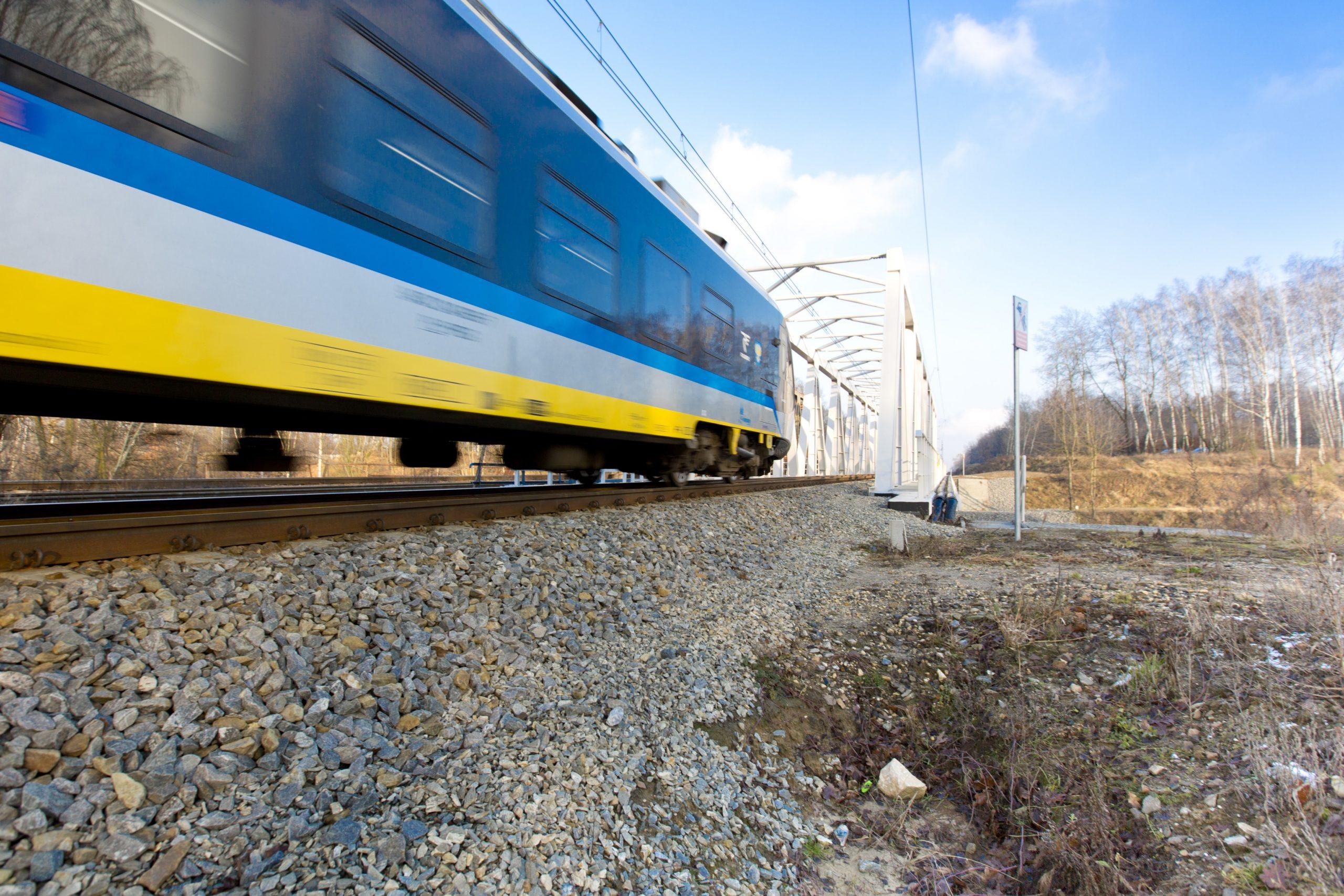 Zdjęcie: pociąg pasażerski wjeżdża na most kolejowy nad Kanałem Kędzierzyńskim.