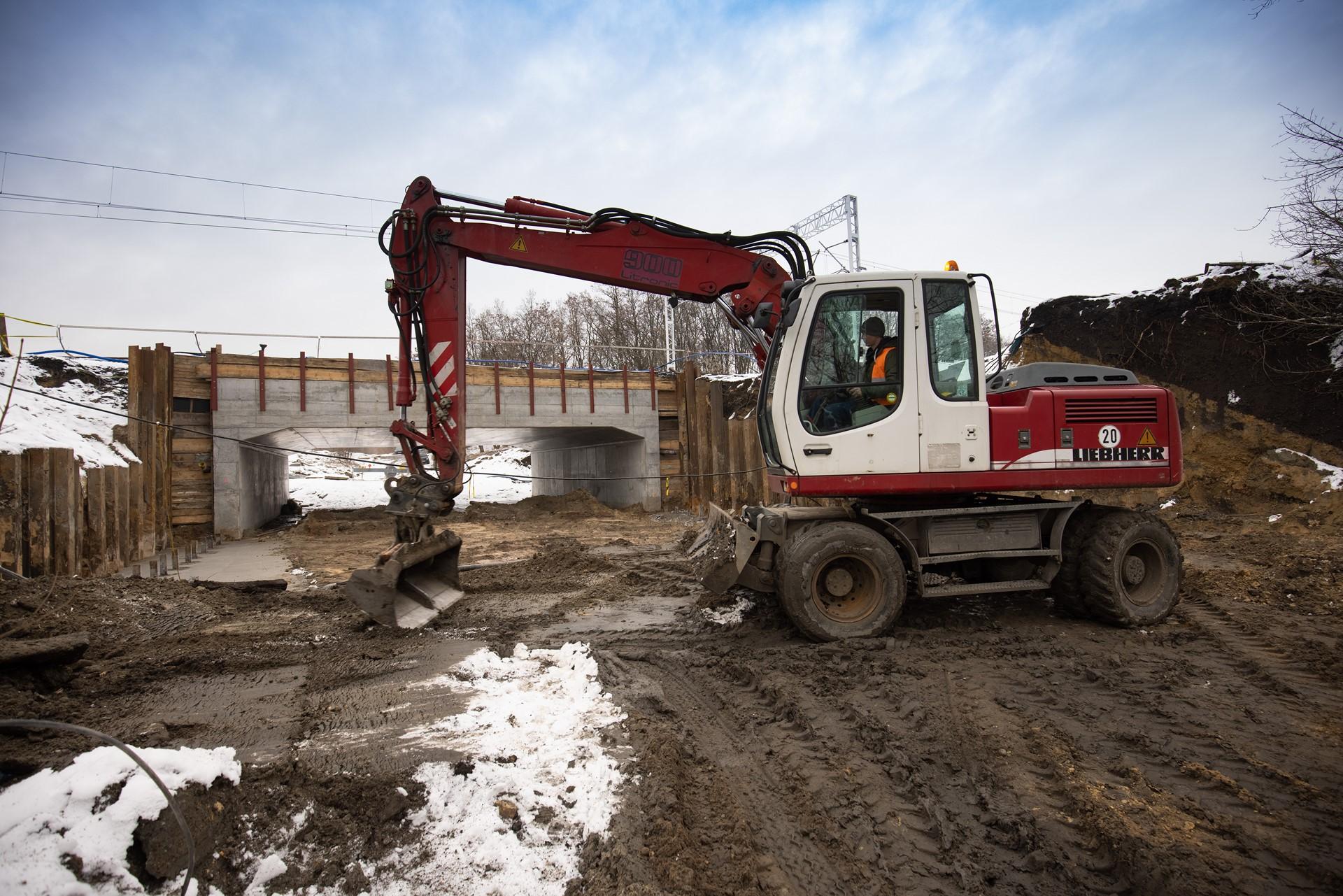 Zdjęcie: czerwony dźwig stoi na budowie, w tle widać nową konstrukcje betonowego wiaduktu.