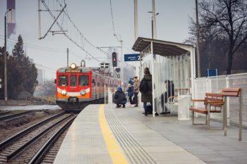 Zdjęcie: pasażerowie czekają na nadjeżdżający pociąg.