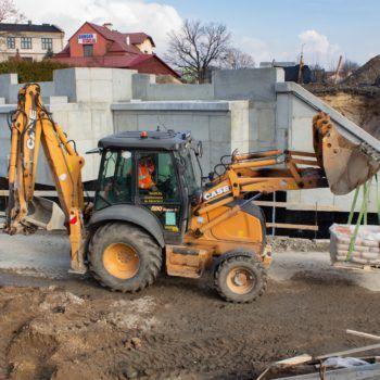 Zdjęcie: koparka wiezie bloki betonowe, w tle betonowa konstrukcja wzmocnienia wiaduktu.