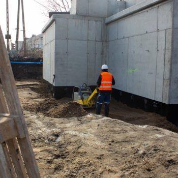 Zdjęcie: robotnik ubija ziemie, w tle betonowa konstrukcja.