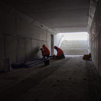 Zdjęcie: dwóch robotników pracuje w ciemnym tunelu.