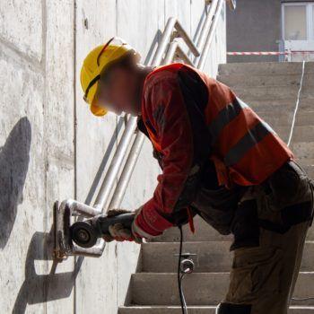 Zdjęcie: robotnik montuje poręcz pry schodach.
