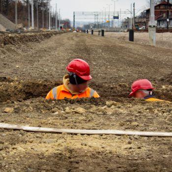 Zdjęcie: dwóch robotników pracuje w ziemi.