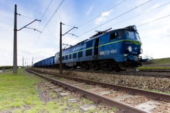 Zdjecie: pociąg towarowy jedzie po torach.