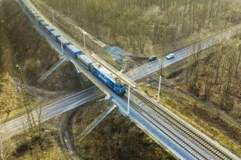 Zdjęcie: widok z góry na wiadukt kolejowo-drogowy przez który jedzie pociąg.