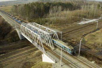 Zdjęcie: widok z góry na wiadukt kolejowo-kolejowy przez który przejeżdża pociąg.