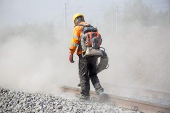 Zdjęcie; robotnik oczyszcza torowisko.