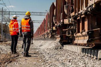 Zdjęcie: dwóch robotników patrzy na pracującą maszynę